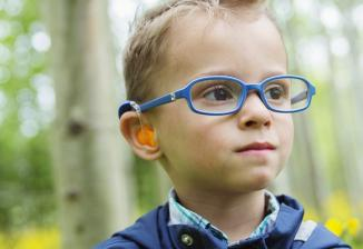 A boy wearing glasses and a hearing device smiles off-camera while standing in a wooded area.