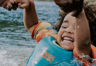 A young child laughs while holding an adult's hands and playing in a lake.