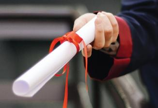 A student in a black robe holding a diploma that is rolled up and tied with red ribbon.