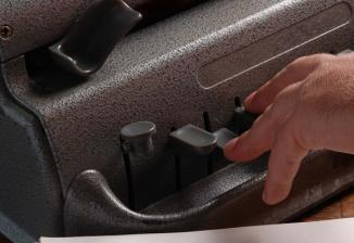 A hand reaches out to touch the keys on a braille writer.