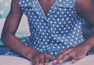 Closeup of a girl wearing a polka-dot dress who is reading braille.