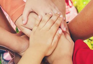 Several children's hands placed on top of each other.