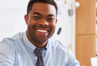 A man wearing a button-down shirt and tie smiles at the camera.