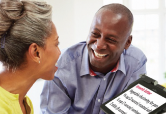 A man and woman smile while using an assistive technology device.