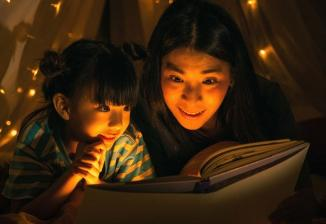 A mother and young child read a book together while laying inside a blanket tent.