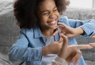 A child smiles while communicating in sign language with an adult.