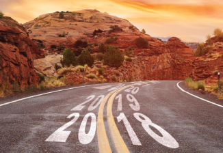 A winding road in a desert setting; years are written in the middle of the road in ascending order.