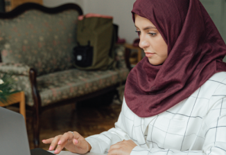 A woman wearing a hijab sits at a table while working on a laptop at home.