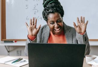A teacher who is sitting in a classroom smiles and waves at an open laptop in front of her.